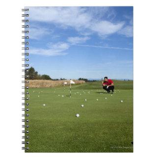 Man lining up a putt while golfing. spiral notebook