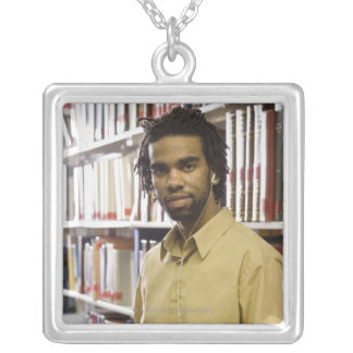 Man listening to music with headphones in square pendant necklace