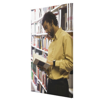 Man looking at book in library canvas print