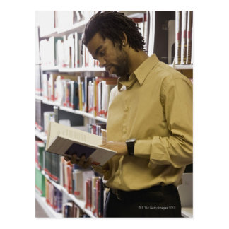 Man looking at book in library postcard