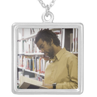 Man looking at book in library silver plated necklace