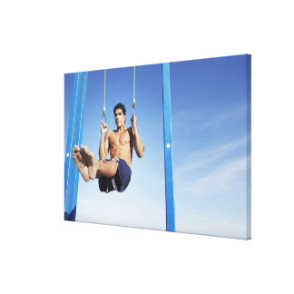 Man on a beach working out on exercise rings canvas print