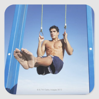 Man on a beach working out on exercise rings square sticker