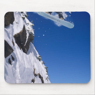 Man on a snowboard jumping off a cornice at mouse mat