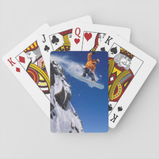 Man on a snowboard jumping off a cornice at playing cards