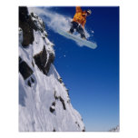 Man on a snowboard jumping off a cornice at poster