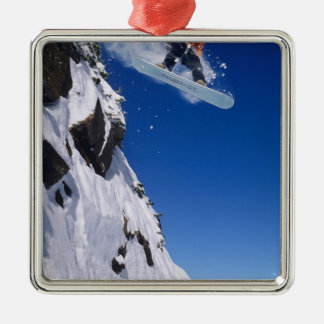Man on a snowboard jumping off a cornice at Silver-Colored square decoration