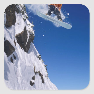 Man on a snowboard jumping off a cornice at square sticker