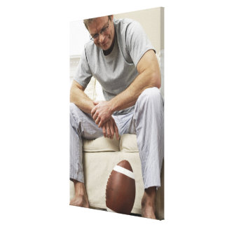 Man on Sofa with Football Canvas Print