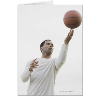 Man playing with basketball, studio shot card