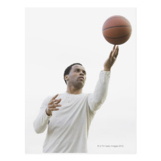 Man playing with basketball, studio shot postcard