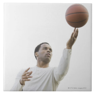 Man playing with basketball, studio shot tile