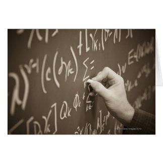 Man printing math equations on a chalkboard card