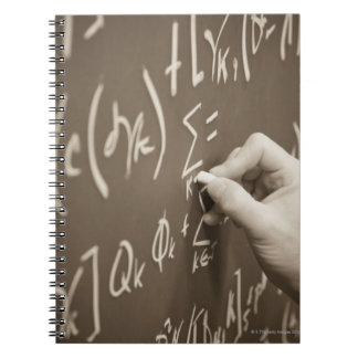 Man printing math equations on a chalkboard notebooks