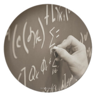 Man printing math equations on a chalkboard plate