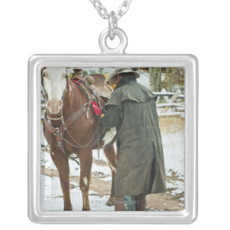 Man putting saddle on horse silver plated necklace