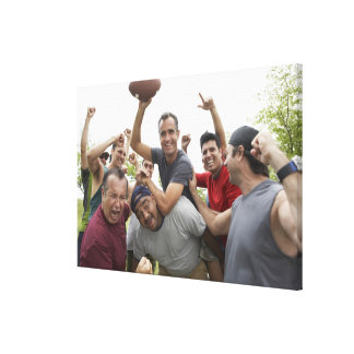 Man raising soccer ball celebrating with friends canvas prints