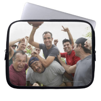 Man raising soccer ball celebrating with friends laptop sleeve