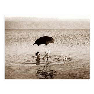 Man reading under umbrella in the Dead Sea Postcard