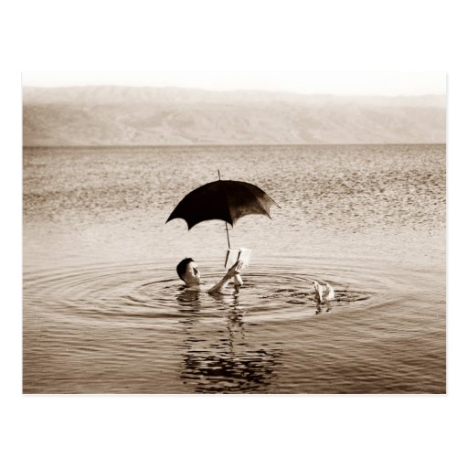 Man reading under umbrella in the Dead Sea Postcard