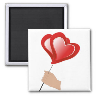 Man's  hand holds red air ball in form of heart square magnet
