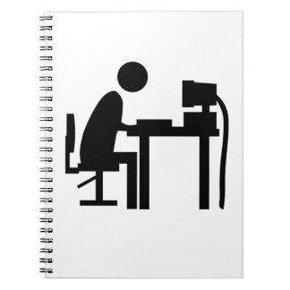 Man sat at a computer. spiral notebook
