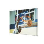Man slam dunking basketball canvas prints