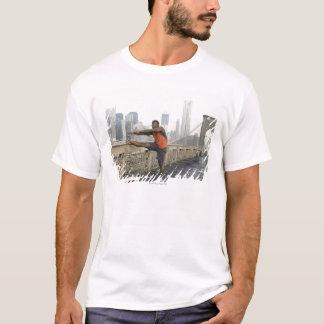Man stretching on brooklyn bridge T-Shirt