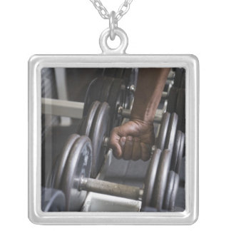 Man taking weight from rack silver plated necklace
