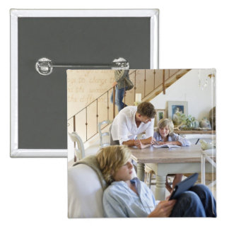 Man talking to little boy with brother using 15 cm square badge
