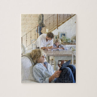 Man talking to little boy with brother using jigsaw puzzle