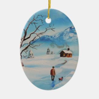 Man walking dog in snow winter mountain scene christmas ornament