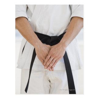 Man wearing karate black belt postcard