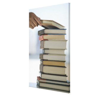 Man's hand taking a book from a stack of books canvas print