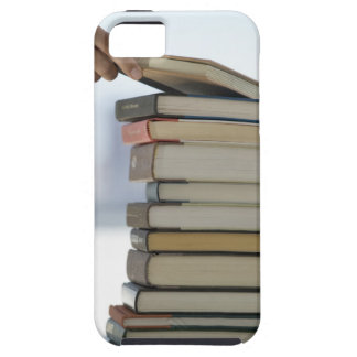 Man's hand taking a book from a stack of books iPhone 5 cover