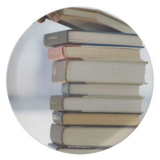 Man's hand taking a book from a stack of books plate