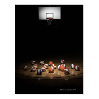 Many basketballs resting on the floor postcards