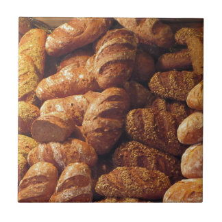 Many mixed breads and rolls background small square tile
