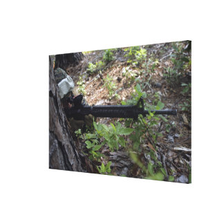 Marine uses a tree for cover and concealment canvas print
