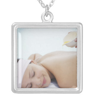 Massage oil being poured on womans back silver plated necklace