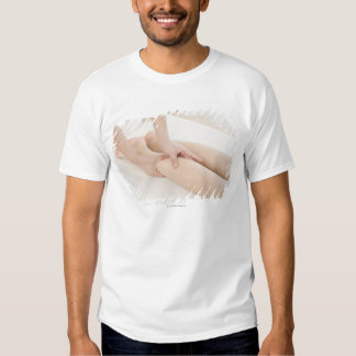 Massage therapist applying foot massage shirt