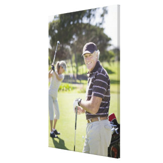 Mature couple playing golf stretched canvas print