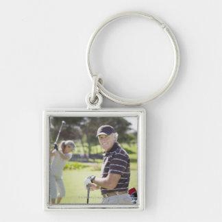 Mature couple playing golf key chain