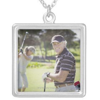 Mature couple playing golf silver plated necklace