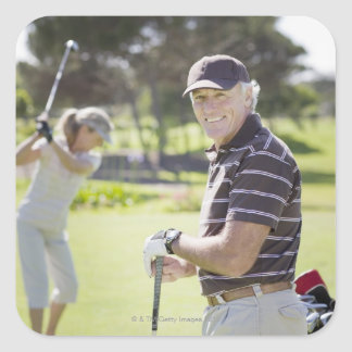 Mature couple playing golf square stickers
