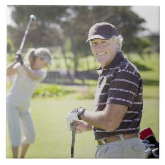 Mature couple playing golf tile