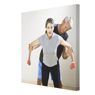 Mature man assisting woman, exercising using canvas print