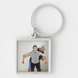 Mature man assisting woman, exercising using keychains