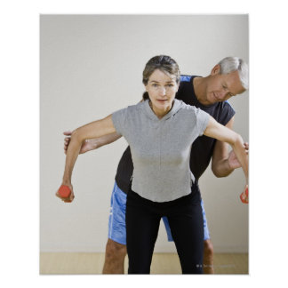 Mature man assisting woman, exercising using poster