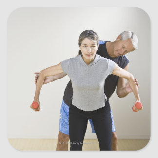 Mature man assisting woman, exercising using square sticker